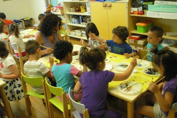 Una insegnante con dei bambini che disegnano