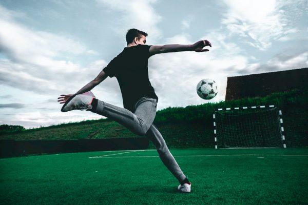 Giovane ragazzo da un calcio ad un pallone